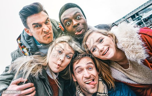 861023492istockphoto Multiracial best friends taking selfie outdoor on autumn winter clothes - Happy youth concept with millennial people having fun together - Multicultural friendship against racism - Bright vivid filter 1185003633