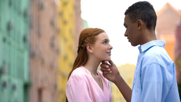 multiracial boyfriend holding girl chin, admiring beloved, intimate moment - kids kiss embarrassed foto e immagini stock