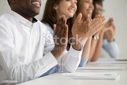 istock Multiracial business audience people applauding sitting at conference table, closeup 1135346400