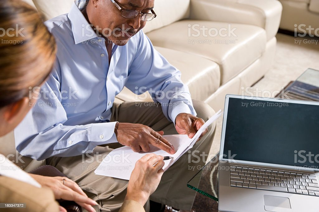 Multiracial business meeting discussing document stock photo