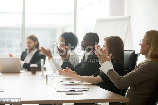 istock Multiracial business people applauding clapping hands at conference meeting table 923039684