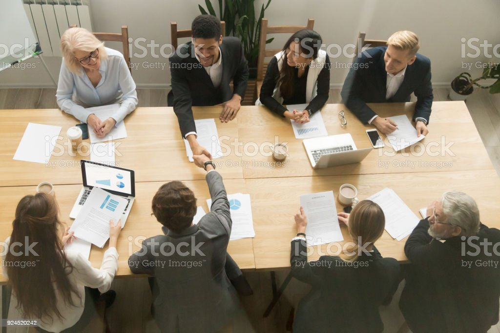 Happy multiracial businessmen shake hands at diverse group meeting,...