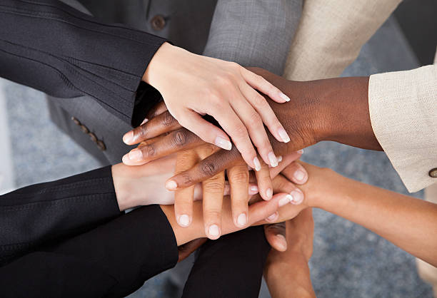 multiracial businesspeople stacking hands - cultures stock pictures, royalty-free photos & images