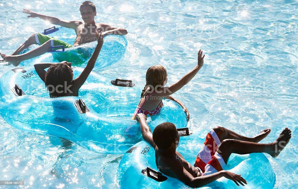 Multiracial children floating on innertubes at water park stock photo