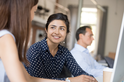 Friendly smiling indian employee female listen colleague girl sitting together at desk in office. Diverse workers talking discussing sharing ideas having busy workday. Manager or mentor teach intern