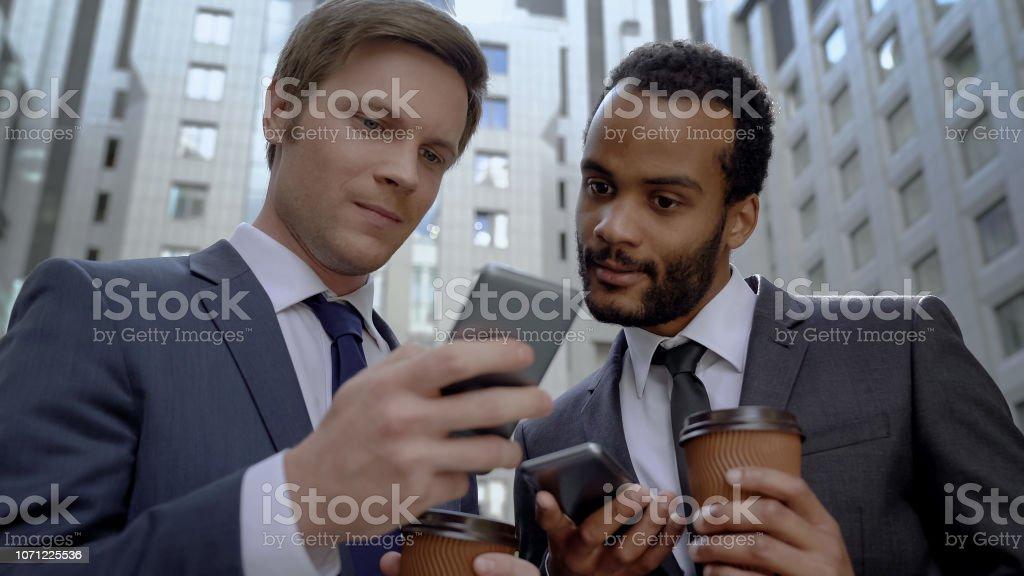 Gemischtrassig Kollegen lesen Nachrichten auf Smartphone zur Kaffeepause, Bürocenter – Foto