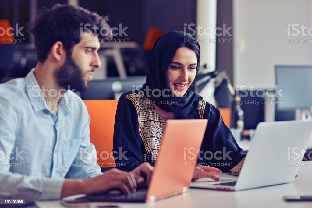 Multiracial contemporary business people working connected with technological devices like tablet and laptop stock photo