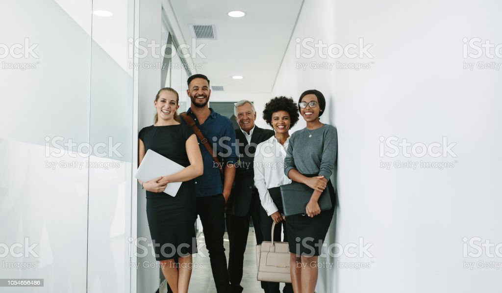 Multiracial corporate professionals in office hallway royalty-free stock photo