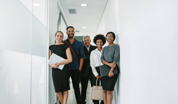 Multiracial corporate professionals in office hallway stock photo