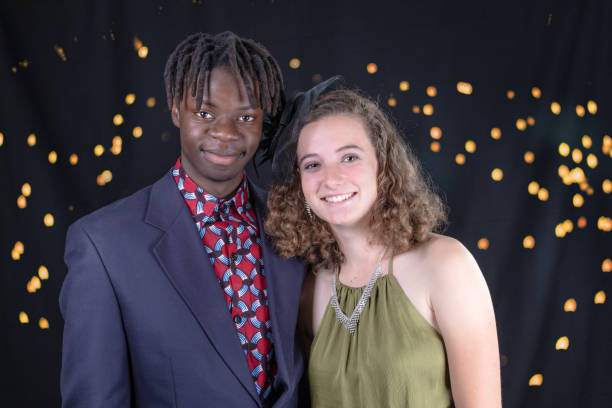 Multi-Racial couple dressed up for a party Studio portrait of a multi-racial couple dressed up for a party against a black background with golden lights prom night stock pictures, royalty-free photos & images
