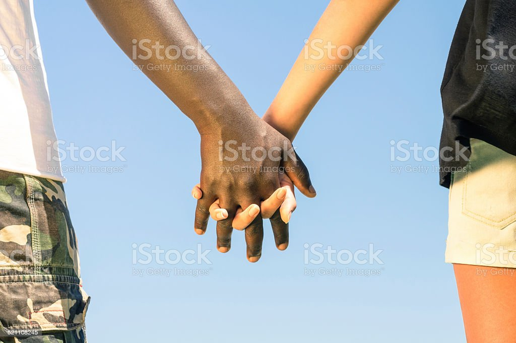 Multiracial couple in love walking hand in hand against racism stock photo