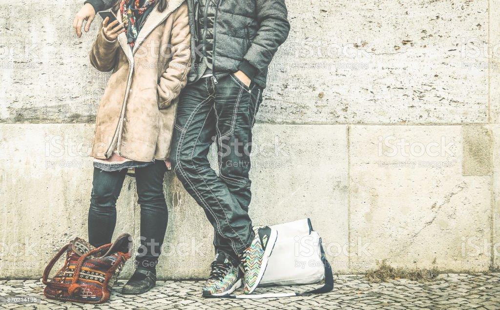Multiracial couple on phase of mutual disinterest using phone - Modern relationship breakup concept on always connected people - City urban lifestyle and everyday life rapport - Retro contrast filter stock photo