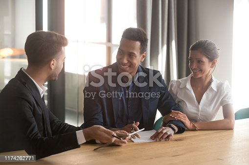 994164754 istock photo Multiracial couple talk with real estate agent discuss buying property 1174262771
