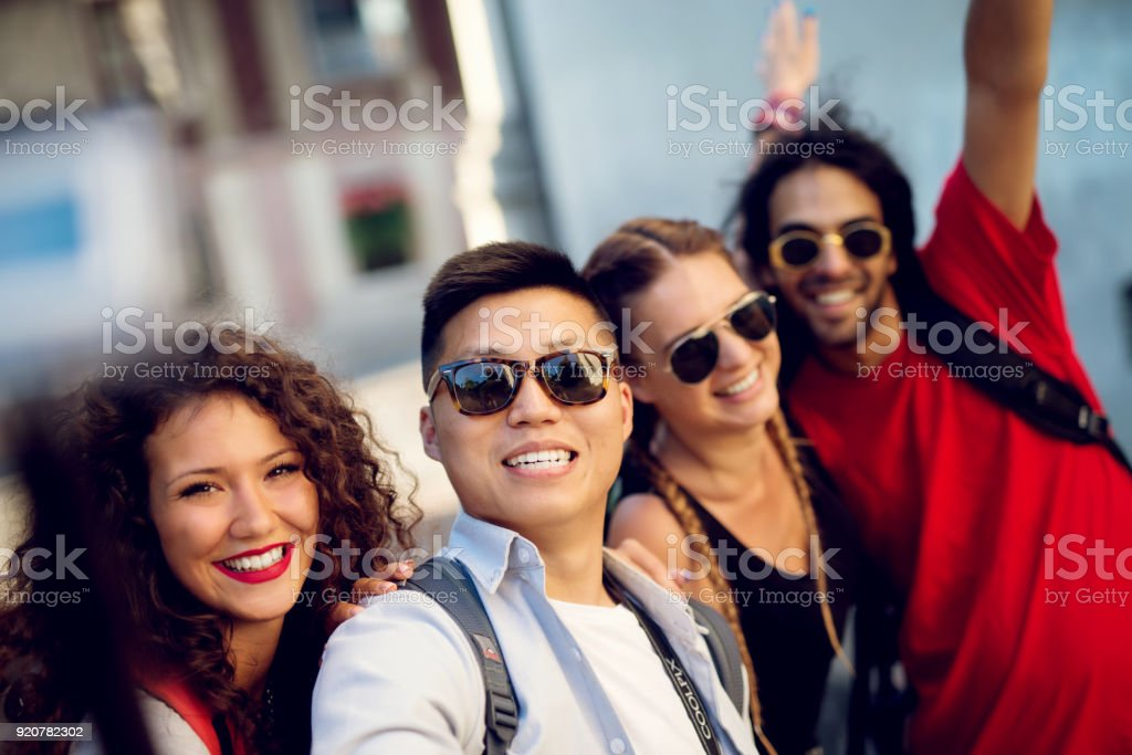 Multiracial couples exploring a city, happy tourists discovering new locations. Making selfie. stock photo