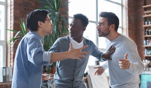 Multiracial coworkers having quarrel in office, conflict of interest stock photo