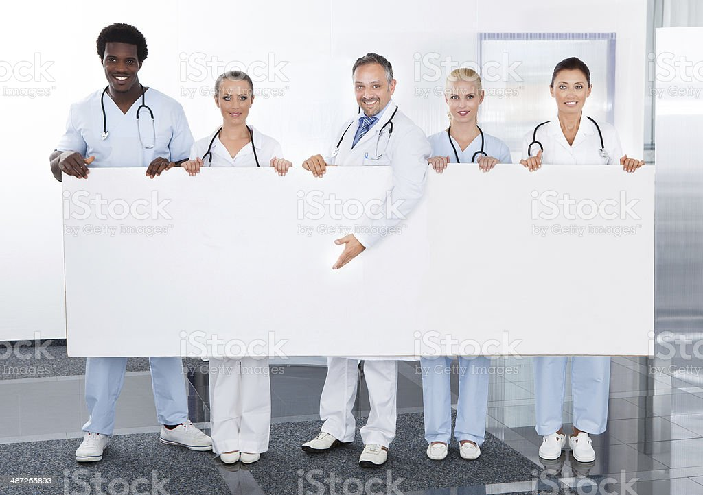 Multiracial Doctors Holding Placard stock photo