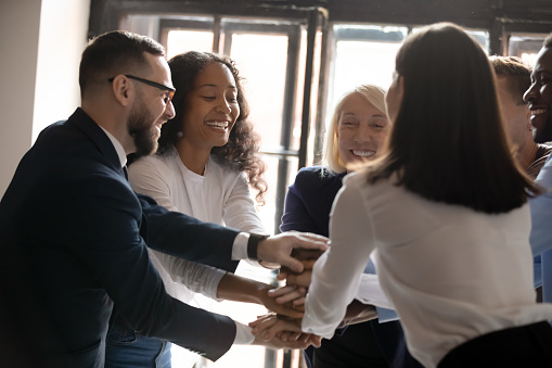 Multiracial entrepreneurs stacked hands together at group meeting celebrating common victory sharing successful project accomplishment, teambuilding activity team spirit, corporate staff power concept