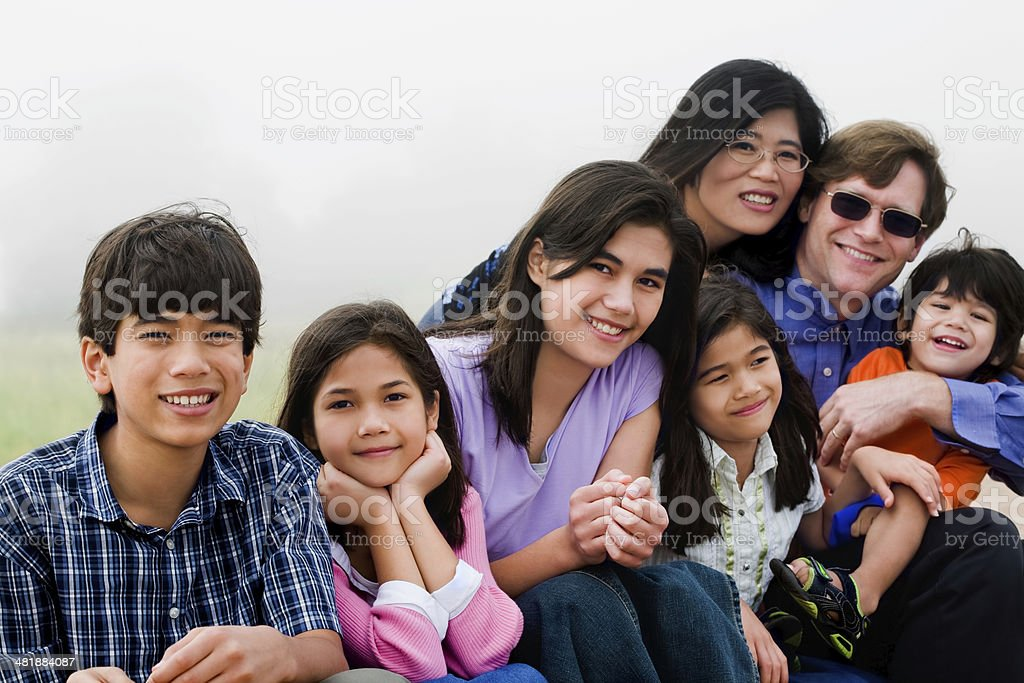 Multiracial family of seven sitting on beach stock photo