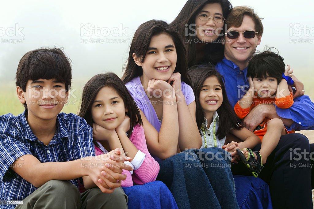 Multiracial family sitting on beach stock photo