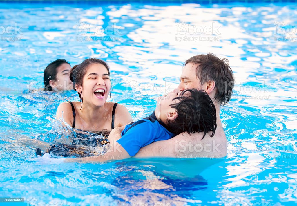 Multiracial family swimming together in pool with disabled youngest son. stock photo