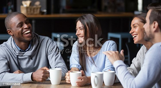 Multiracial friends girls and guys having fun laughing drinking coffee tea in coffeehouse, happy diverse young people talking joking sitting together at cafe table, multicultural friendship concept
