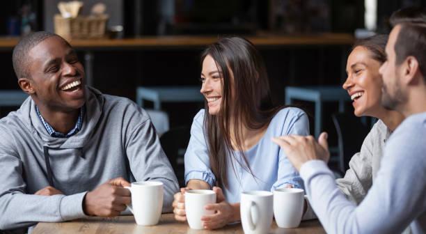 wielorasowe przyjaciele dziewczyny i faceci bawiąc się śmiejąc się pijąc kawę - przyjaźń zdjęcia i obrazy z banku zdjęć