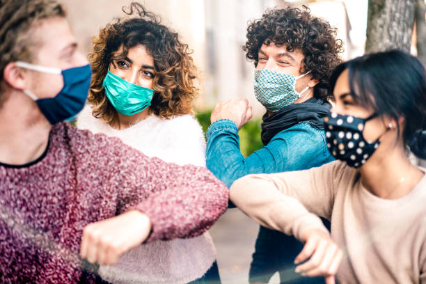 Multiracial friends greeting with elbow bump wearing face protection - New normal lifestyle concept with young people covered by disposable mask - Selective focus on middle left woman stock photo