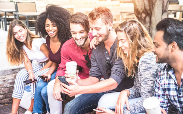 Multiracial friends group using smartphone at university college - Young people addicted by mobile smart phone - Technology concept with connected trendy millennials - Soft pink pastel sunshine filter stock photo