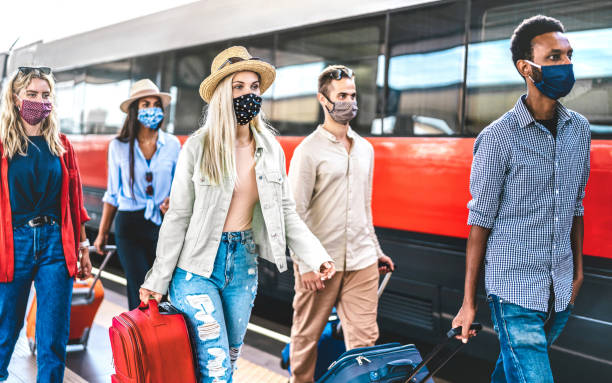 Multiracial friends group walking at railway station platform - New normal travel concept with young travelers on social distancing and face covered by protective mask - Focus on blonde girl with hat stock photo