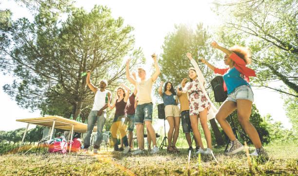 gemischtrassig freunde, die spaß am grill pic nic gartenparty - freundschaft multikulturelle konzept mit glücklichen jugendlichen trinken und tanzen sie im frühlingsurlaub camp - sonnenschein halo grün filter - tanz camp stock-fotos und bilder