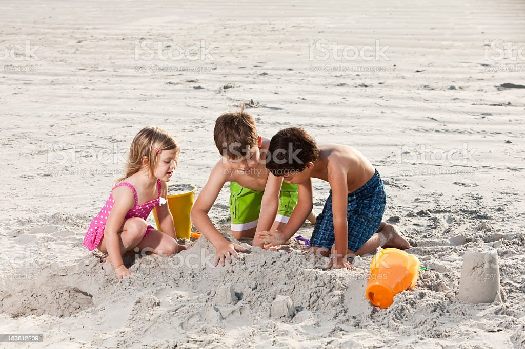 Multiracial friends playing in sand at the beach royalty-free stock photo