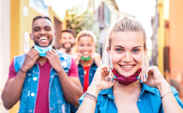 Multiracial friends smiling with face mask after lockdown reopening - New normal friendship concept with guys and girls having fun together on travel vacation - Bright filter with focus on right woman stock photo