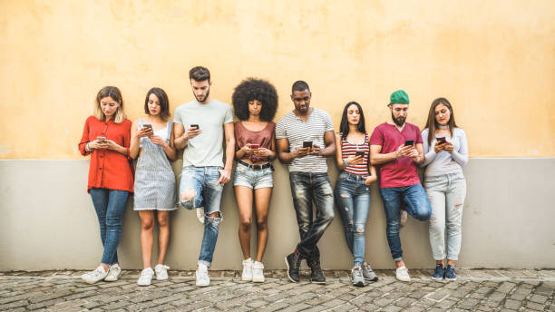 multiracial friends using smartphone against wall at university college backyard - young people addicted by mobile smart phone - technology concept with always connected millennials - filter image - ragazzi adolescenti foto e immagini stock