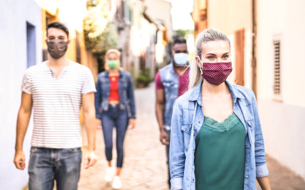 Multiracial friends walking with face mask after lockdown reopening - New normal friendship concept with guys and girls spending time together on city streets - Warm filter with focus on right woman stock photo