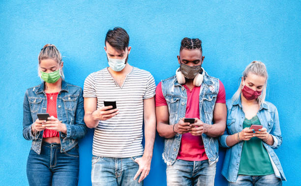Multiracial friends with face masks using tracking app with mobile smart phones - Young millenial people sharing content on social media networks - New normal lifestyle concept - Bright vivid filter stock photo