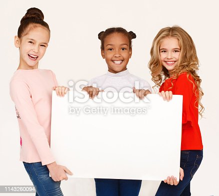 istock Multiracial girls holding blank banner for advertisement 1143260094