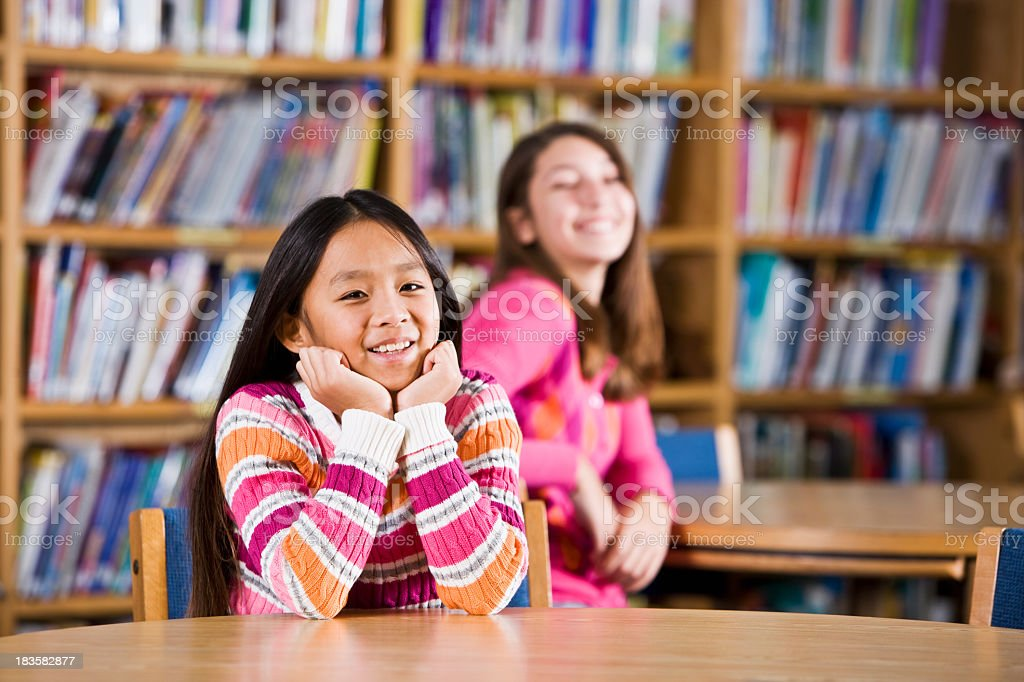 Multiracial girls sitting in school library royalty-free stock photo