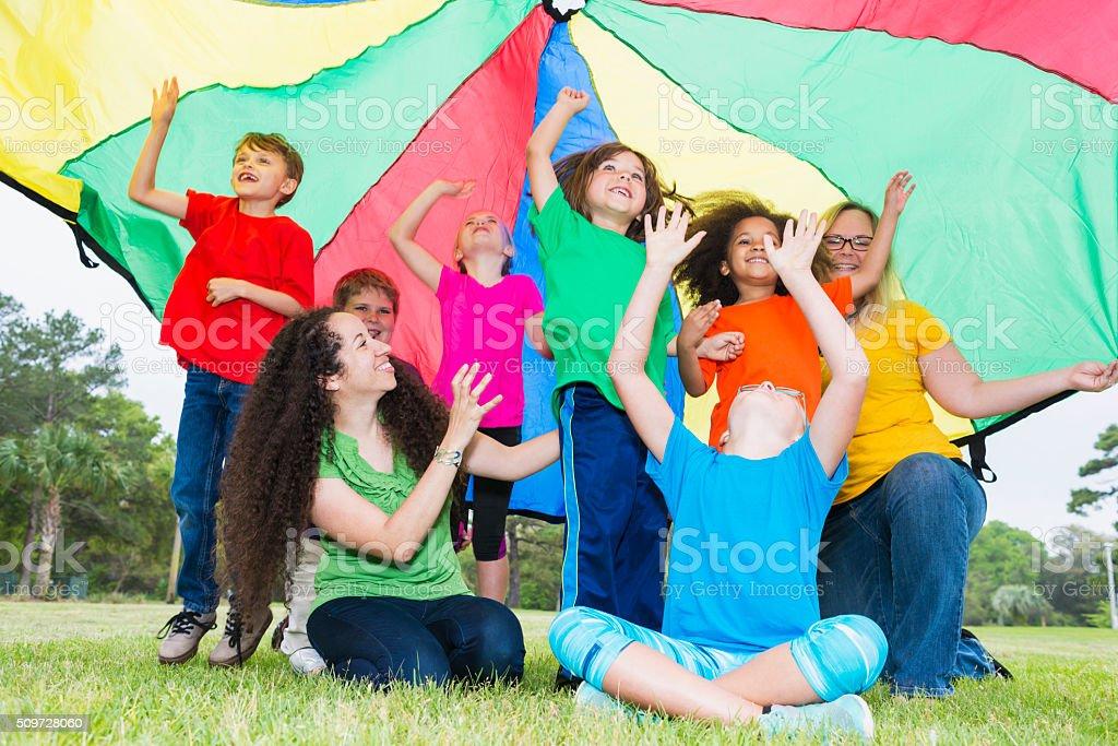 Groupe multi-ethnique de l'enfant, moniteurs au camp d'été - Photo
