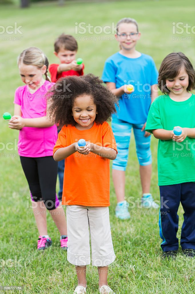 Multiracial group of children in an egg spoon race stock photo