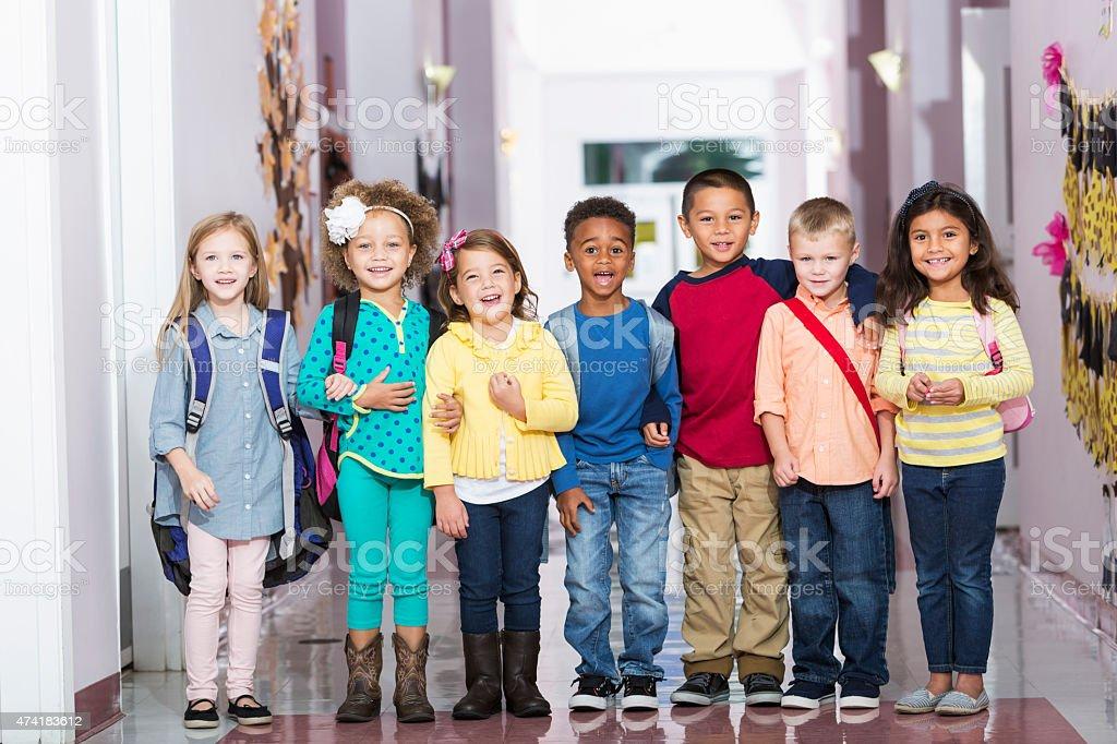 Multiracial group of children in preschool hallway stock photo