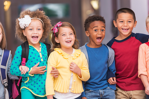 A multi-ethnic group of children standing in a row in a school hallway, excited and laughing, watching something.  They are in kindergarten or preschool, carrying bookbags.  They are 4 to 6 years old.