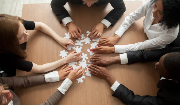 Multiracial group of colleagues engaging in assembling puzzle, top view stock photo
