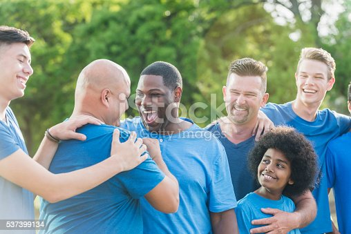 1091098220 istock photo Multi-racial group of fathers and sons in blue shirts 537399134