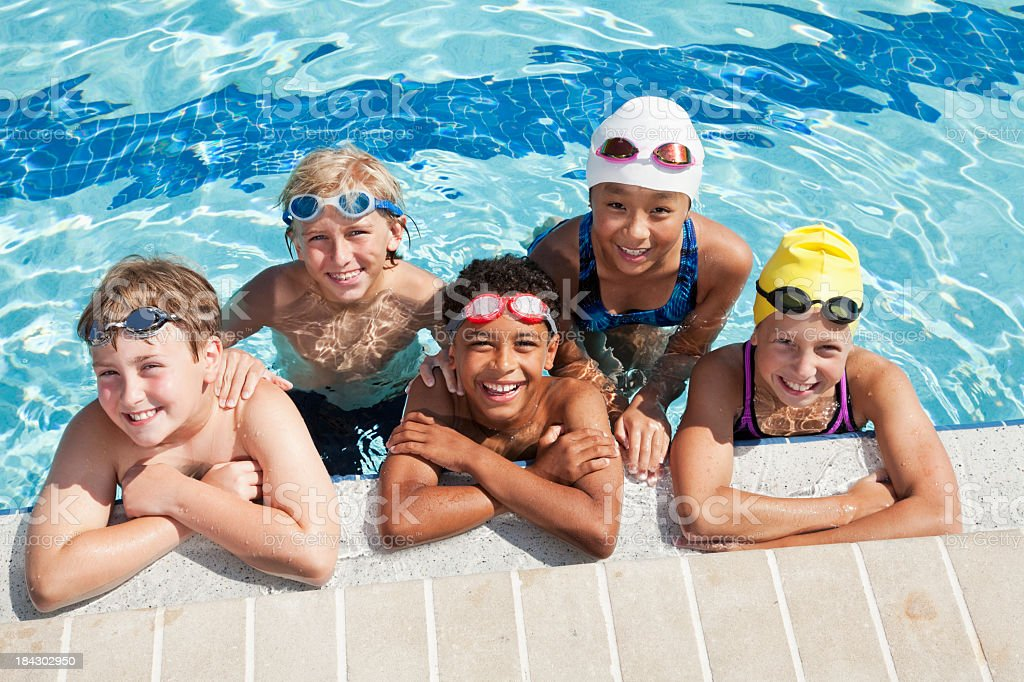 Multiracial group of five children in swimming pool stock photo