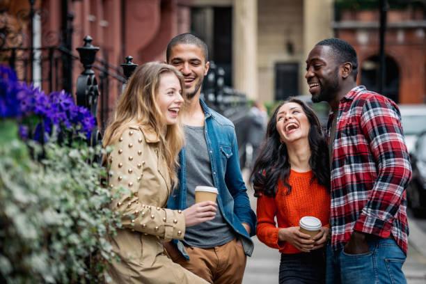 Gemischtrassigen Gruppe von Freunden Spaß zusammen in London. Zwei Mädchen und zwei jungen, redeten und lachten. Wohnquartier mit Häusern und Autos auf Hintergrund. Lifestyle und Freundschaft Konzepte. – Foto