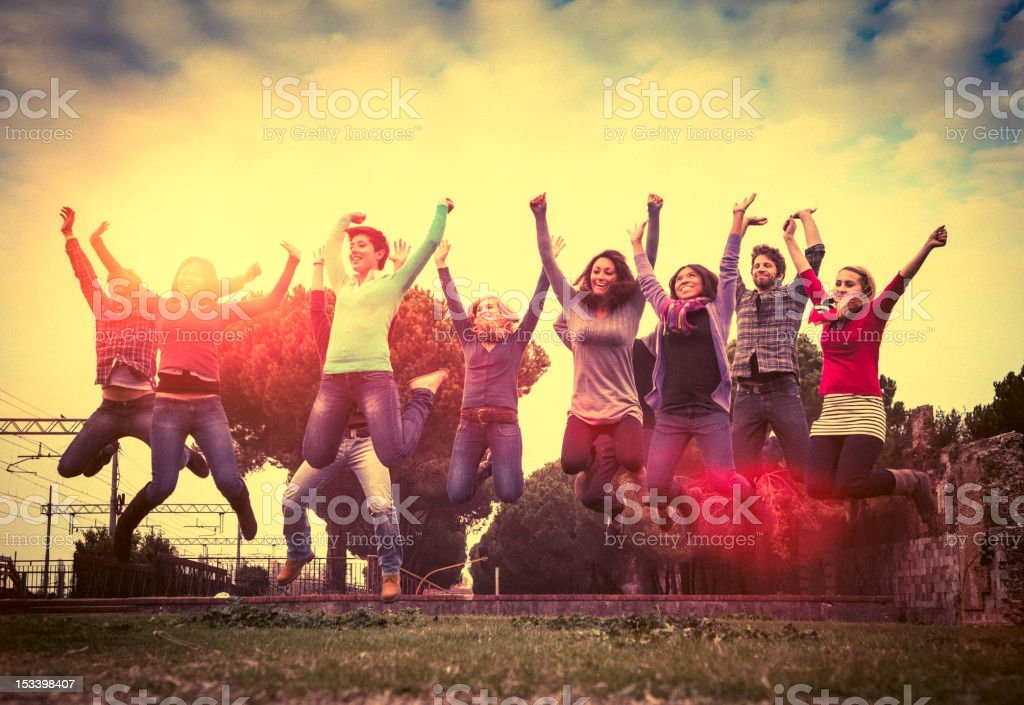 Multiracial group of friends jumping on the park royalty-free stock photo