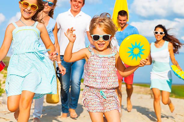 multiracial group of friends walking at the beach - outdoor sonnenschutz stock-fotos und bilder