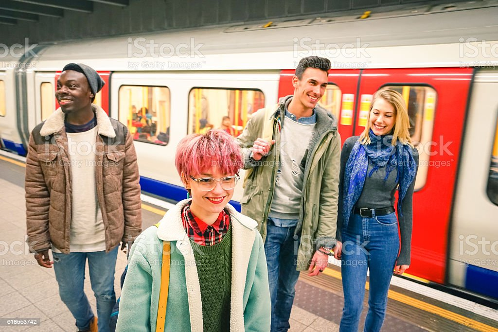 Multiracial group of hipster friends having fun in tube subway stock photo