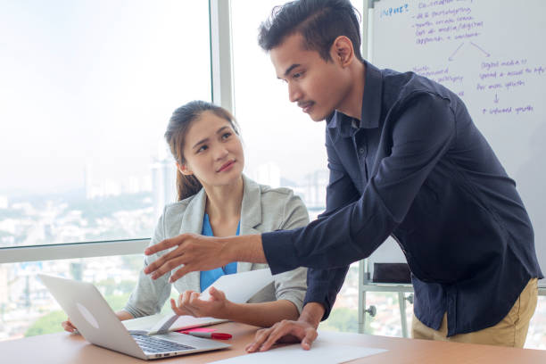 multiracial group of man and woman gather in a meeting room, discussing business plan together. multiracial group of man and woman gather in a meeting room, discussing business plan together. university student presenting and explaining homeworks to the lecturer business Malaysia stock pictures, royalty-free photos & images