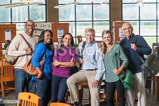 876965270 istock photo Multiracial group of mature students in library 473032092